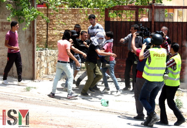 Muhammed Mhaid being carried from his home to the ambulance by protesters
