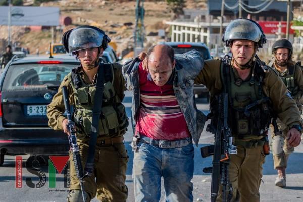 An injured Palestinian man being taken away by soldiers