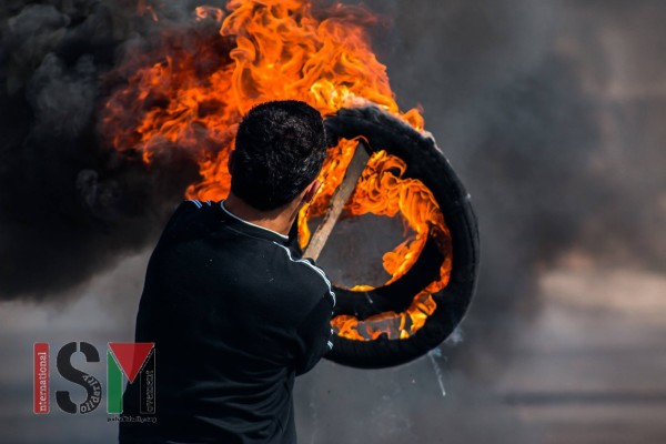 Palestinian with burning tires