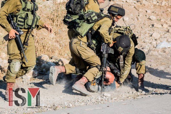 Soldiers forcing a Palestinian on the ground