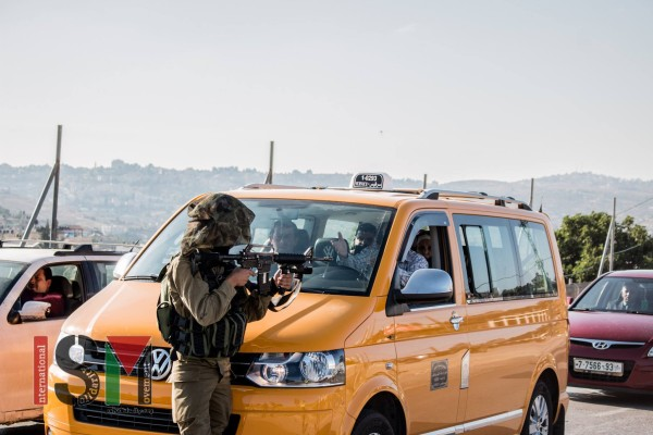 An Israeli soldier using a taxi full of people as a shield