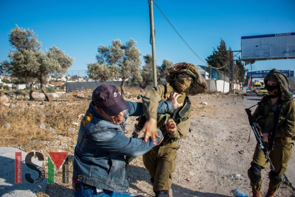 Israeli soldier hitting a Palestinian man