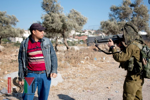 Israeli soldier pointing his gun in the face of a Palestinian man