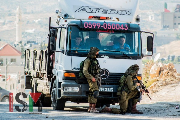 Israeli soldiers using a truck with passengers as a shield