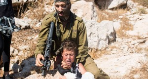 Israili soldier strangulationa Palestinian boy at non violent demonstration in Nabi Saleh. Photo credit: Karam