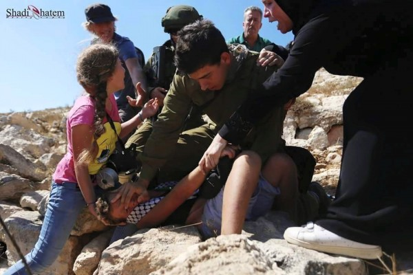 Israili soldier attacking Palestininan boy at non violent demonstration in Nabi Saleh. Photo credit: Karam