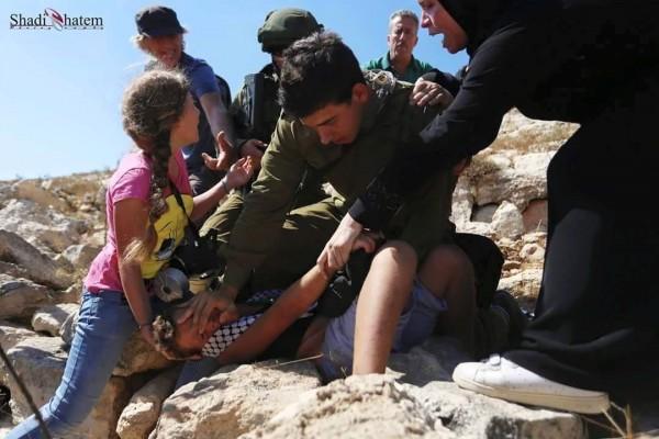 Israili soldier attacking Palestininan boy at non violent demonstration in Nabi Saleh. Photo credit: Karam