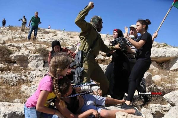 Israili soldier threatning Palestinian women and children at non violent demonstration in Nabi Saleh. Photo credit: Karam