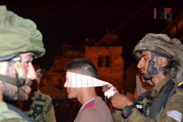 The soldier handcuffed and blindfolded a Palestinian young man