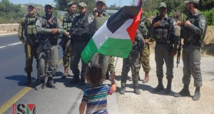 A Palestinian child protests in front of Israeli soldiers near Beit El Baraka