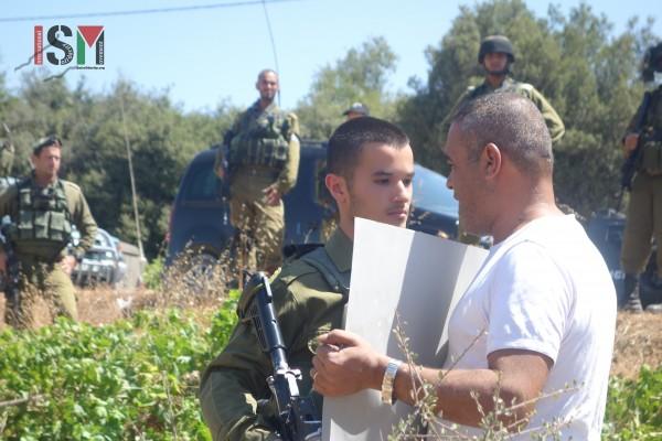 Israeli soldier confront a nonviolent Palestinian protestor near Beit El Baraka