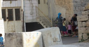 Settler women with their children blocking the stairs to the Abu Rajab house