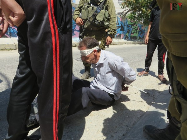 Palestinian man sitting on the ground in pain