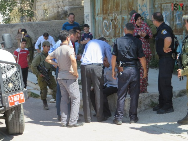Police, bystanders and the soldiers standing around Hisham