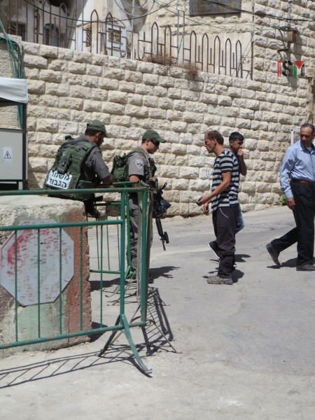 Palestinian man searched by Israeli soldiers