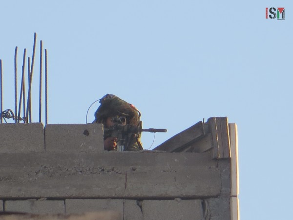 Israeli soldier shooting rubber-coated steel bullet from a Palesitnian house