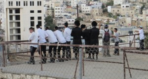 Settlers stand on the roof of a Palestinian home watching Israeli forces attacking Palestinians nearby.