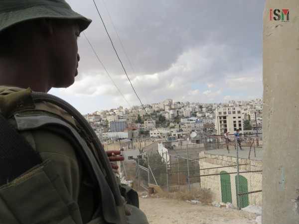 Israeli soldier stands idly by as settlers invade Palestinian roof, attack female monitor.