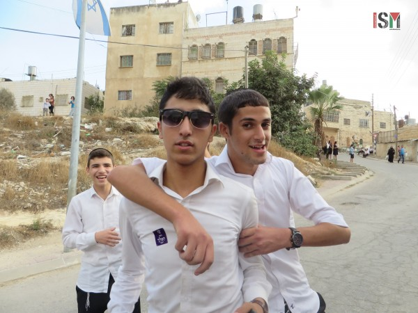 Settlers boys pose jovially for photos after spitting and cursing at human rights monitors and shouting racial slurs about Arabs.