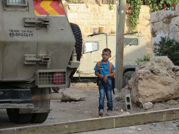 Small boy forced to pass Israeli forces' armored trucks
