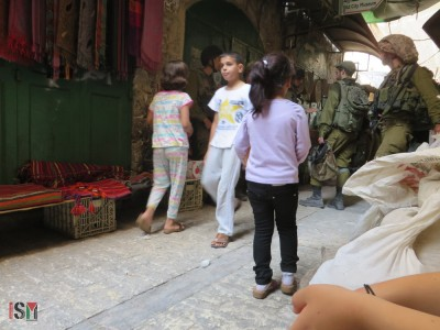 Group of children having to pass Israeli soldiers blocking the Palestinian market