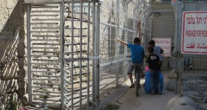 Palestinian children forced to wait at a checkpoint for soldiers to allow them to pass