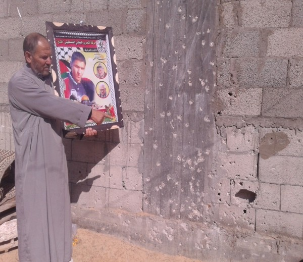 Dr. Mohammed's father holding the picture of his 22 year old martyred son, Ahmed and pointing to the exact place where he was murdered while trying to help a woman. Photo ISM