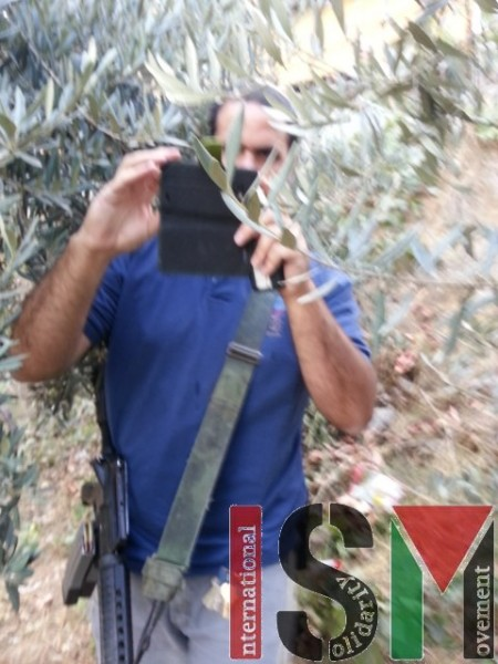 Machine gun armed settler taking the Pictures of the international volunteers