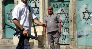 Armed settler walks past a Palestinian man on Shuhada Street in al-Khalil. Photo Credit: The Atlanic