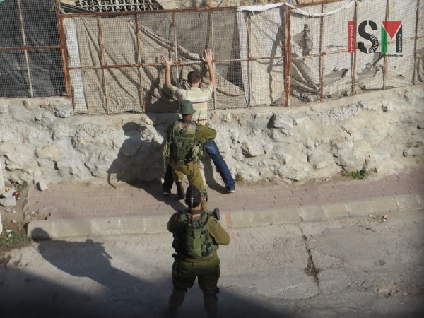 Palestinian man being body searched this morning in Tel Rumeida as part of new 'security measures' in Khalil.