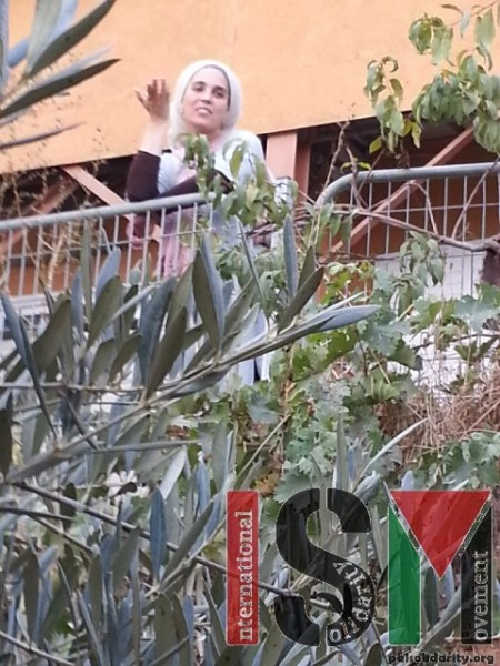 A settler woman laughs as she and two others harass Palestinian farmers and international monitors.