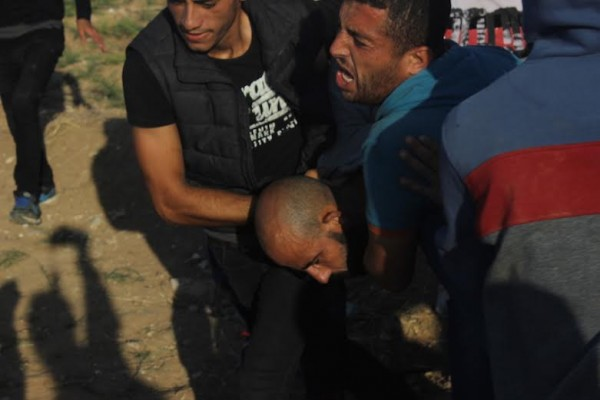 Injured Palestinian carried away