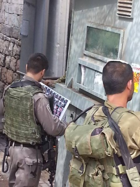Israeli forces look over a poster of photos of young Palestinians they wish to arrest while detaining young man in metal box.