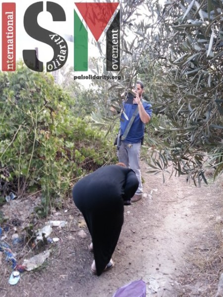 Machine gun armed settler photographs a Palestinian woman as she tries to harvest on her land.