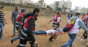 Medic rush to evacuate the injured at a demonstration near the Beit El settlement.