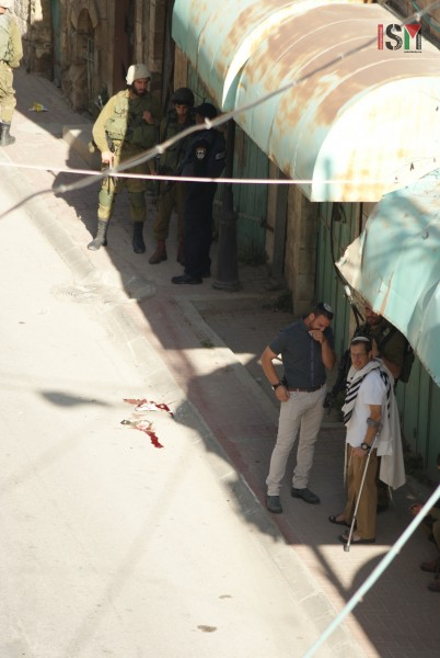 Israeli settlers standing right next to the scene of the execution