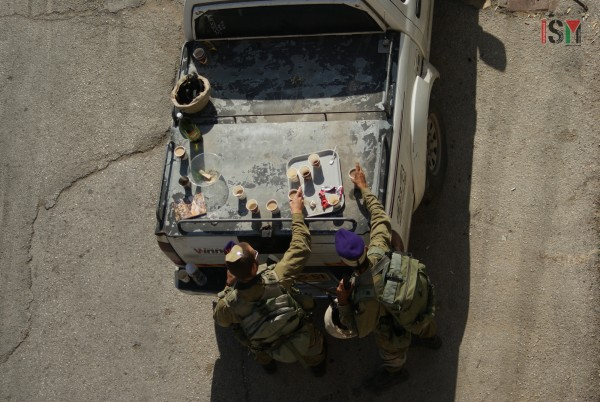 Israeli soldiers having tea brought by settlers