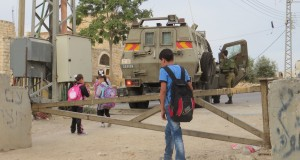 Palestinian schoolchildren forced to squeeze past armored Israeli jeep on their way to school