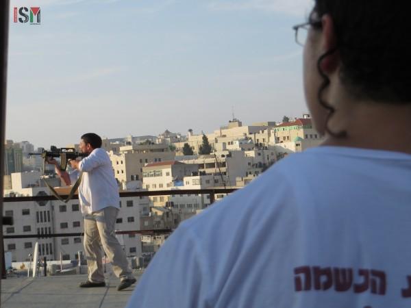 Israeli settler pointing his gun at Palestinian families