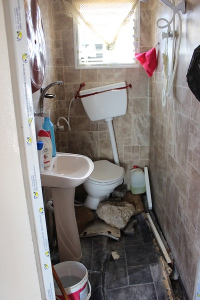 The bathroom in Fatima Abdel Aziz Qudaih's home with the floor broken from the pressure of the floods. Photo credit ISM