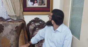 Khader Adnan looks in a mirror at himself at his home