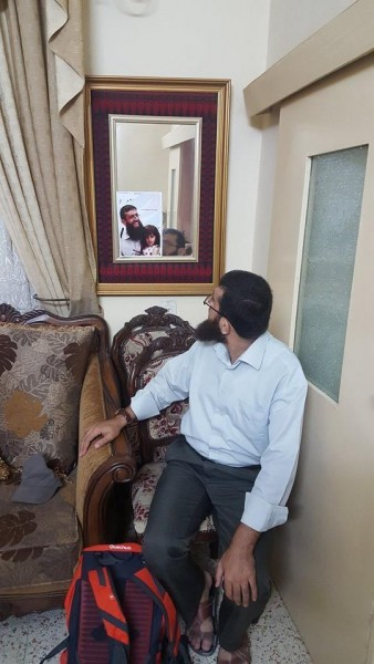 Khader Adnan looks in a mirror at himself at his home