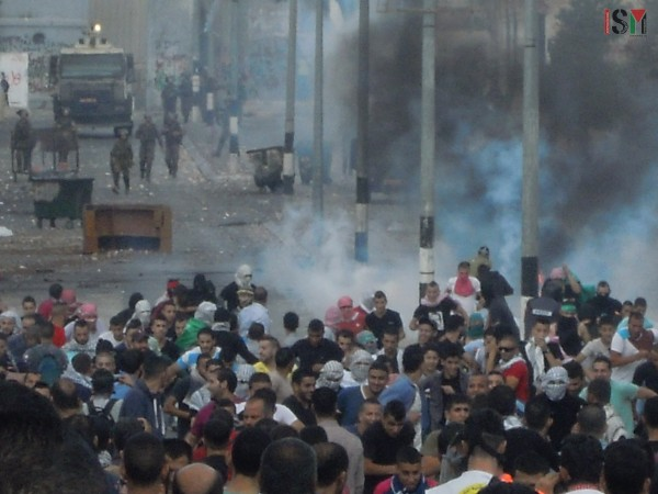 Palestinians running from the tear-gas