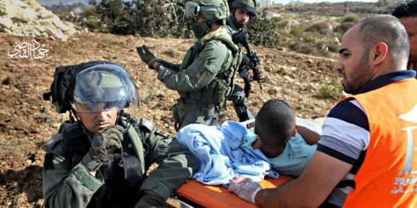 Medics crews on the field carry an injured demonstrator despite soldiers' harassment