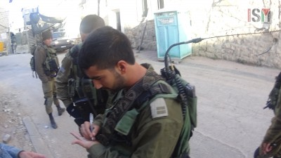 Israeli soldier writing down passport number of an international
