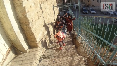 School-children climbing the stairs to their school