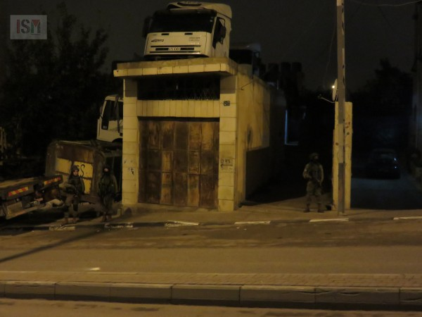 Soldiers on street while the unit searches Palestinian house with flashlight