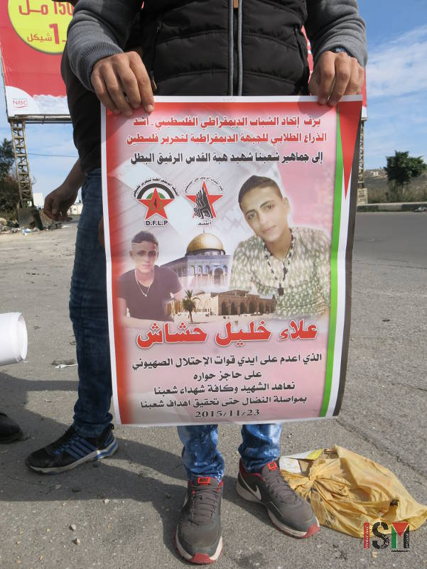 Palestinian youth holding poster with the name and picture of his friend, Alaa Khalil Hashash, who was killed on November 23rd .