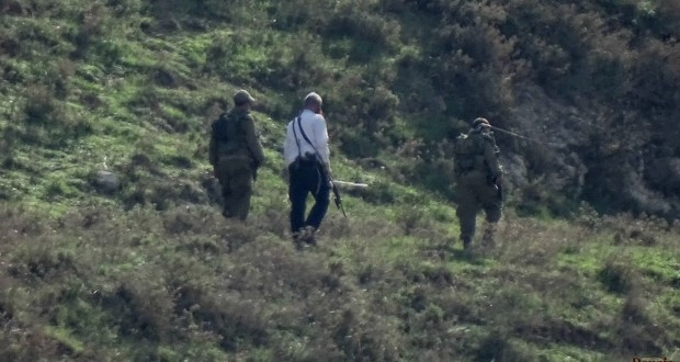 1 illegal settler hiking on the hills around Madama, accompanied by 2 israeli soldiers.