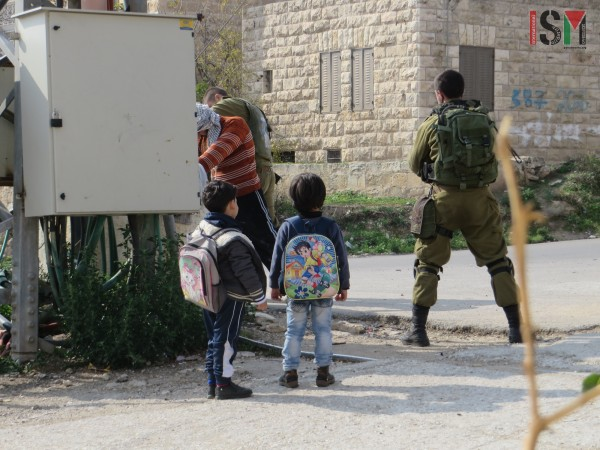 Two boys watch Israeli forces body-searching their father